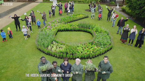 Volunteers and staff stand beside the beautiful floral 6, part of the Opening Ceremony of the Commonwealth Games
